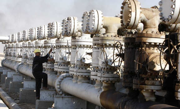 A worker adjusts the valve of an oil pipe in a south Rumaila oil field, south of Basra